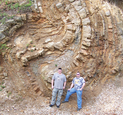 Mineralogy class students are posing for scale at a series of folds at the Brady Mountain Dam near Hot Springs, Arkansas.
