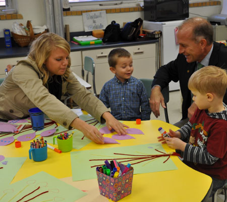 Adrian College President Jeffrey R. Docking and AC Teacher Education Student Taylor Hudson with students at the YMCA Preschool at Lincoln Elementary.