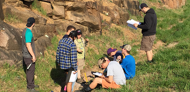 Dr. Hanson lecturing about an unusual mineral locality during the Petrology course field trip to Missouri (Spring 2017)