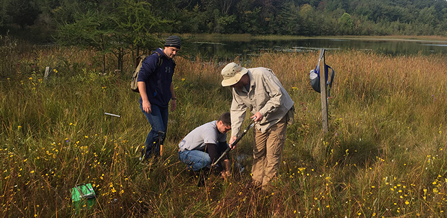 Dr. Muntean instructing students installing a sampling device to measure spring dischage at Adrian College's Walden West property.